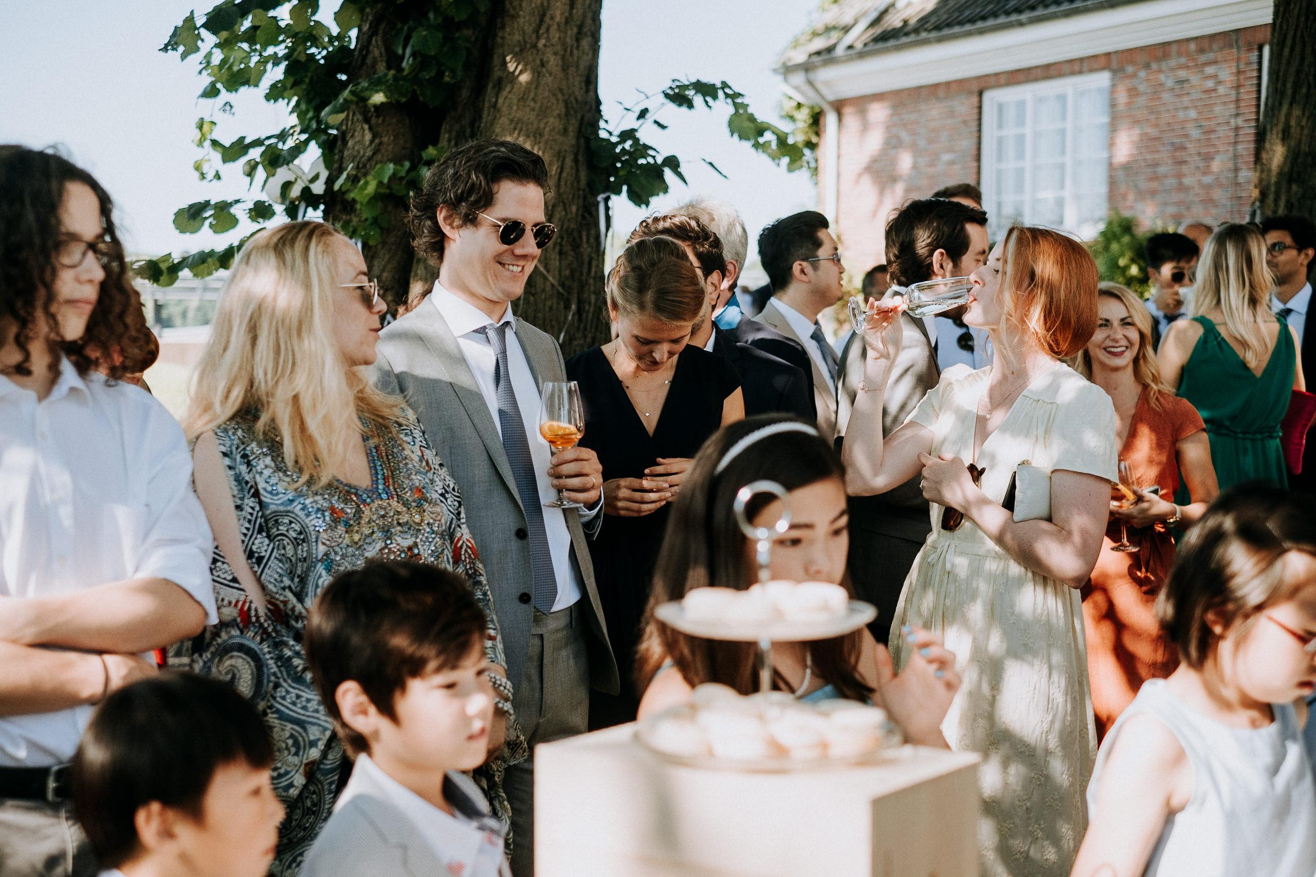 Hochzeitsgäste essen Torte und trinken Prosecco auf einem Hochzeitsempfang in der Villa am Jachthafen